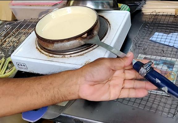 把沾有蛋漿的鑊放在電熱爐上加熱。