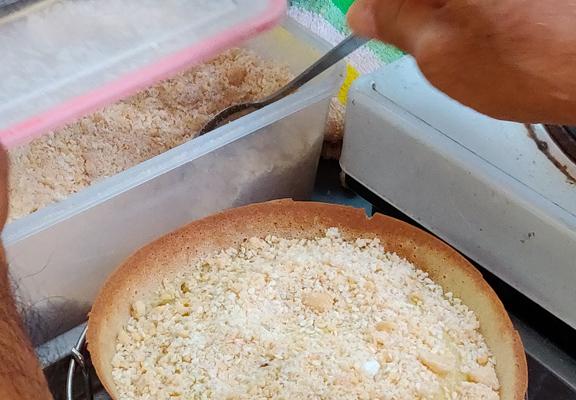 餅底烘好後取出,撒上預先混好的餡料。餡料內有砂糖、花生碎及芝麻。