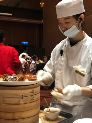 服務員以「摩打手」快速地用鴨肉包著米飯握成壽司。