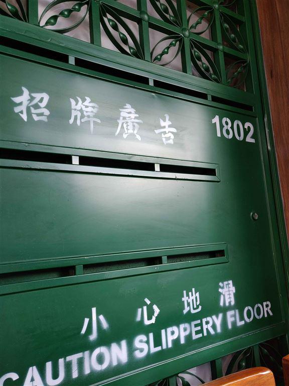大門旁一角嘅裝飾擺設,扮舊通花鐵閘,上面噴咗「小心地滑」幾個字,令人舊記憶返晒嚟。