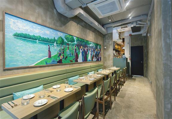 牆上掛上一幅長壁畫,畫中描繪法國人在岸邊舉行派對聚會嘅快樂時光,為餐廳營造輕鬆悠閒嘅氣圍。