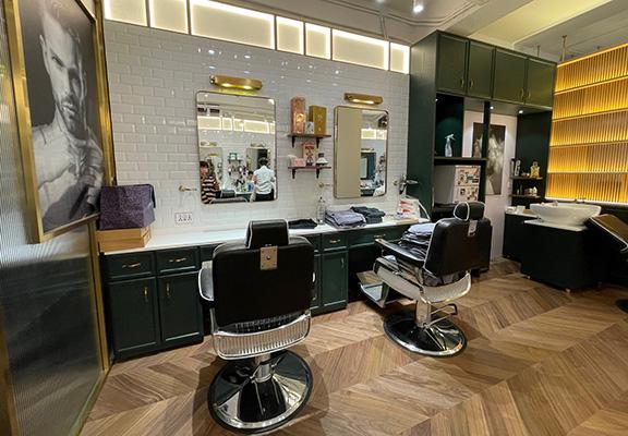 白色瓷磚牆身配上金屬黃銅材質嘅家具和黑色真皮理髮椅,大玩懷舊格調。